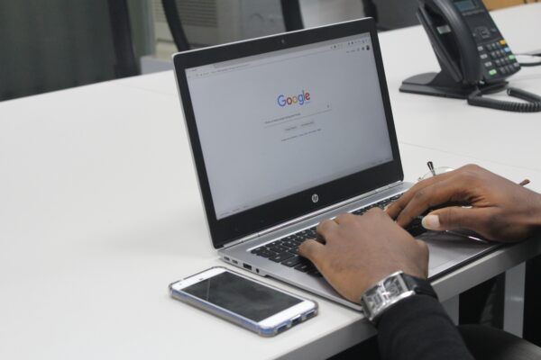 Man Typing on Google on a Laptop